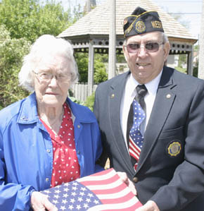 Myrna Noble accepts the Mini-Park Flag from Dale Bowman, representing the American Legion.