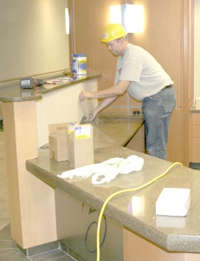 Josh Probasko, construction project manager, installs a panel in the new front desk area.