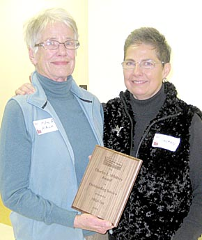 Mitzi Fox, left, accepts the Charles L. Whitney Award for Outstanding Service from Colleen Babcock of Lincoln during the Prairie Plains Resource Institute's annual meeting