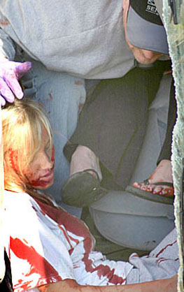 Emergency responder reaches one of the victims in the overturned van during Saturday's drill.