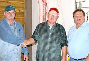 FIRST HOG — Dave Kolm (center) brought the first hog to be processed at Cedar Rapids Locker, LLC. Flanking him are Maynard Pelster, left, and Brian Yosten, right.