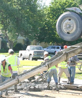 Workers pour concrete on Marengo Street in Albion Tuesday morning.