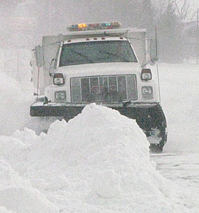 City of Albion snowplow clears a large drift in the downtown area.