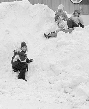 Children play in a snow pile near Boone Central Middle School.