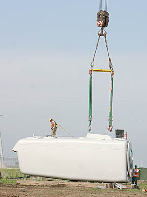 A worker at the TPW wind farm prepares a nacelle to be lifted by a crane.