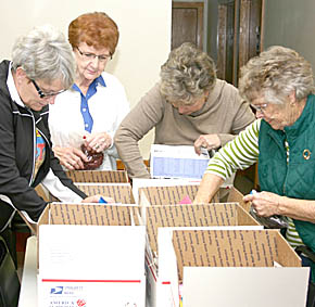 VFW Auxiliary members preparing the gift boxes for troops.