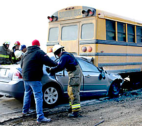 Firemen work at the scene of the car-bus crash north of Albion last Friday, Feb. 24.