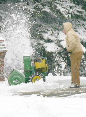 Albion resident uses a snow blower to clear snow from his driveway last Saturday.