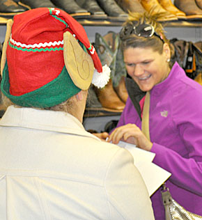 A Christmas elf visits Angie Reardon at the Boot Rack in Albion.