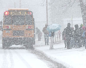 Bus loads students in April 22 snowstorm.