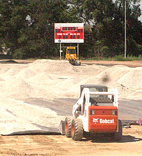 Rock spreading operation at Boone Central football field and track.