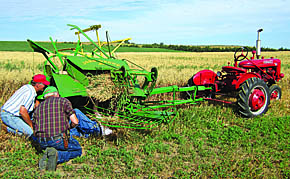 Rae Valley Heritage Association make some repairs to the machinery while cutting oats recently for Rae Valley Days.