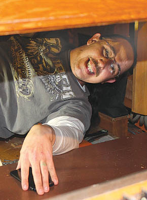 Organ repairman Clifford Burnette at work under the pipe organ at the Albion United Methodist Church.