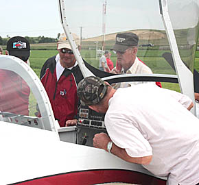Airplane enthusiasts lean in for a closer look at an experimental airplane on display Sunday at the Albion Airport.