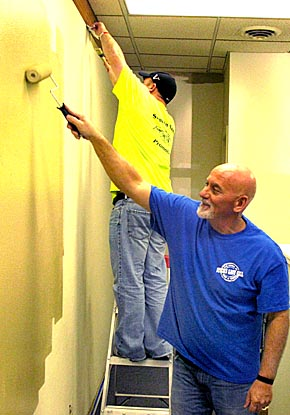 Mike and Shay Robinson paint the interior of the new Green Crop Inc. office in Albion.