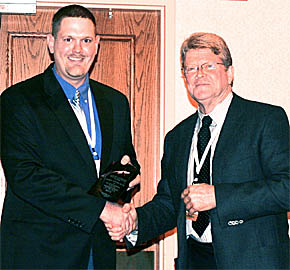 Dr. Jeremy Young, left. accepts his award from Dr. Rick Cockerill. am associate in the Town and Country Vet Clinic and past president of the Nebraska Veterinary Medical Association.