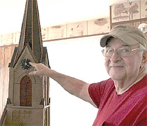 Bill Parks points to the working clock in the steeple of his St. Boniface Church scale model.