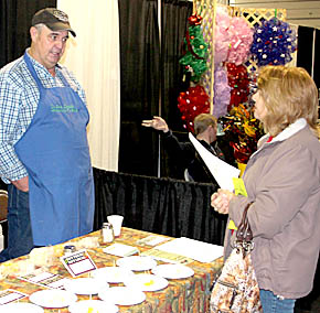 Bob Bernt of Clear Creek Farms, Spalding, discusses his cheese with the customer at the Home, Farm & Garden Show.