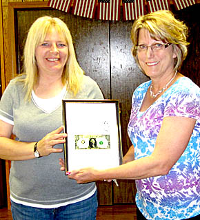 Tina Henn, l., presents the First Dollar award to Kathy Seier.