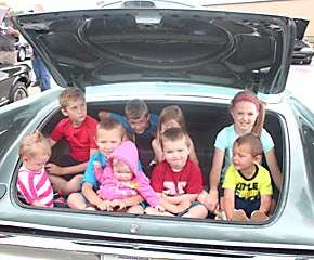 A 1959 Chrysler Imperial trunk will hold nine children with room to spare. These kids demonstrated the size of the trunk during the annual Smoke n Chrome Car Show last Saturday.