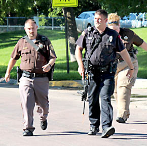 "Sheriff's deputies John Buck and Pam Stapleman, and Albion Police officer Joe Predmore approach the school after being notified of an ""active shooter"" in the building."