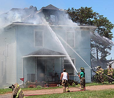 Area firemen battle a house fire near Newman Grove Tuesday.