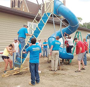 Valero employees and parish members build a new playground structure at St. Michael's School.