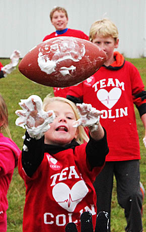 It's tough to throw a football with whipped cream on your hands. This was one of the obstacles for children participating in the Team Colin obstacle course last Saturday.