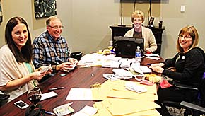 REASON TO SMILE -- Boone County Philanthropy Council officers (l.-r.) Tina Stokes, Jay Wolf, Julie Mahoney and Cheri Werner add up donations from the Boone County Big Give during the Wrap Party Friday evening, Dec. 5, at the Cardinal Inn.