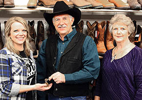 Dani Thober, l., new owner of The Boot Rack, takes the keys from Norm and Darlene Reynoldson.