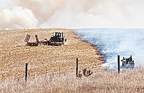 Firemen are assisted by a farmer with a tractor and disc at the north end of Friday's fire.