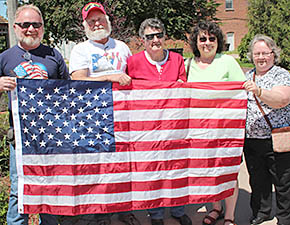 Florence Streeter and her children with the flag raised in her honor at Albion's downtown mini-park.