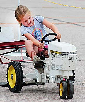 Young tractor driver gives it all she's got.