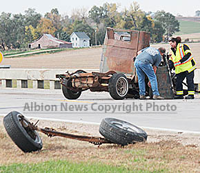 Fire and Sheriff's Department personnel collect pieces from the vehicle involved in the Highway 14 accident just north of Albion.