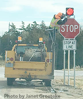 Department of Roads installs stop signs at 14-56 junction.