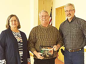 Carlsons receive an appreciation plaque from Fair Board President Dave Noble.