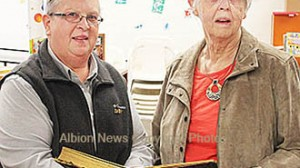 Marion Brickel, right, accepts the Houtz family photo book from Pat Wagner.