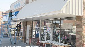 New metal awning under construction at Wells Hallmark.
