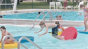 Youngsters jump on the lily pad feature at the local pool.