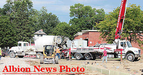 Concrete truck dumps the first load into a pumper truck for distribution on the site.
