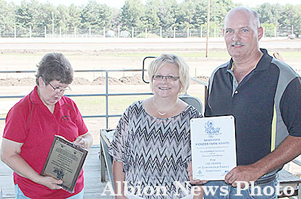 Jeryl Kettelson presents the Pioneer Farm Award to Sharon and Jim Karmann.