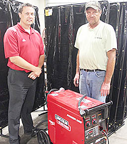Boone Central High School Principal Erik Kravig, l., and welding instructor Gary Hoefer with one of the new mig, stick, tig welders in the school shop.