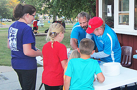 Dale Salber and Bruce Werner were scooping ice cream for waiting children during the outdoor movie night at the Petersburg Park on Aug. 20.