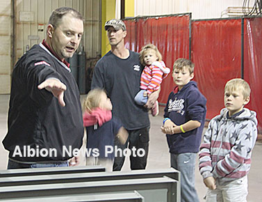 Sentinel Manufacturing Manager Mark Prososki explains painting processes used in the plant to Brad Scheffler and his family during a tour