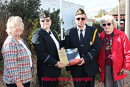 Leon Magsamen, third from left, received the annual Living Veteran Award during the Veterans Day program last Friday, Nov. 11. Shown with Magsamen at the mini-park flag raising in his honor are, l.-r., presenter Fern Medlin, American Legion Post 162 Commander Tina Landauer, and his wife, Margaret.