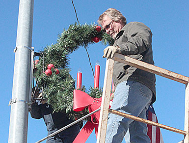 Curt Berglund and Steve Gragert installed Albion's downtown Christmas decorations on Sunday, Nov. 13.