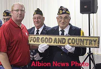 Chad Martinsen, left, presents an engraved wooden plaque to veteran Harold Miller of Albion.