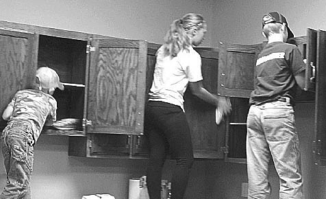 Cleaning cabinets in new parish hall.