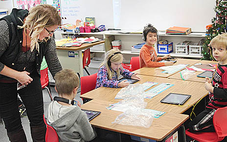 "Trina Hellbusch, technology coordinator at Boone Central Public Schools, works with students in Mrs. Anderson's kindergarten classroom during the ""Hour of Code"" last week."