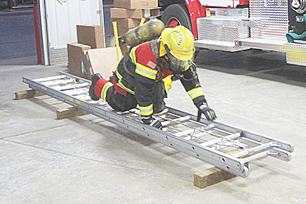 Fireman Marc Pelster crawls on a ladder, which simulated the rafters of a building.